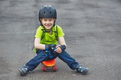 Boy in helmet posing with skateboard Stock Images