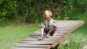 A boy in a helmet lies on a swing. A boy in a helmet and protection on his arms and legs lays on a wide swing stock footage