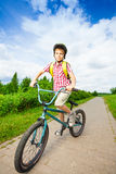 Boy in helmet rides his bike along the road Royalty Free Stock Photography