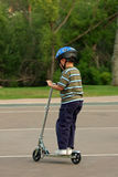 Boy with helmet rides scooter Royalty Free Stock Image