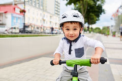 Boy in a helmet riding bike. In the city park Royalty Free Stock Images