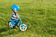 Boy in helmet riding a blue balance bike run bike Stock Images
