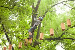 Child in a adventure playground. A boy in a helmet and safety equipment in adventure ropes park on the background of nature Stock Photos