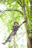 Child in a adventure playground. Boy in a helmet and safety equipment in adventure ropes park get down in the end of way Stock Photos