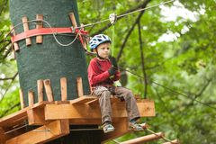 Child in a adventure playground. Boy in a helmet and safety equipment in adventure ropes park get down in the end of way Royalty Free Stock Photography