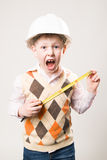 Boy in a helmet with a tape measure and emotionally shouts Stock Images