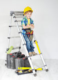 Boy with helmet and tool belt on stepladder Stock Images