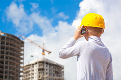 Boy in a helmet with toy radio looking at building Stock Photo