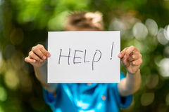 Boy with Help sign Stock Photo