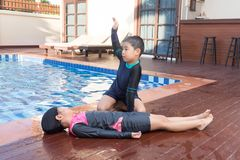 Boy helping drowning child girl in swimming pool by doing CPR. stock photography