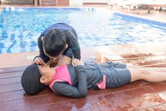Boy helping drowning child girl in swimming pool by doing CPR. Boy helping drowning child girl in swimming pool by doing CPR stock images