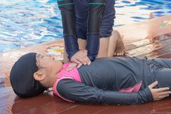 Boy helping drowning child girl in swimming pool by doing CPR. Boy helping drowning child girl in swimming pool by doing CPR stock photography