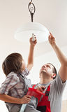 Boy helping father mounting a ceiling lamp - screwing in the lightbulb stock photo
