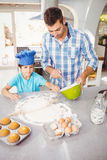 Boy helping father in preparing food. High angle view of boy helping father in preparing food at home Royalty Free Stock Photos