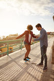 Boy helping girlfriend to keep her balance. Boyfriend showing girl how to skateboard while holding her hand tightly and gesturing with the other while she has Royalty Free Stock Image