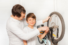 Boy helping his father repairing bicycle brakes Royalty Free Stock Photo