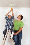 Boy helping his father to paint the room. Sitting on top of ladder Stock Photography