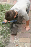 Boy Helping With Home Improvement. Boy helping with the repair of a sidewalk by removing bricks to re-position them Royalty Free Stock Image