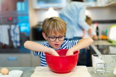 Boy helping mother in kitchen. Learning to bake Royalty Free Stock Photography