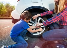 Boy helping mother to change tyre using lug wrench royalty free stock photography