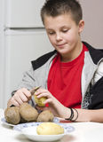 Boy helping mum in kitchen. A teenage boy helping his mother in the kitchen, peeling potatoes Royalty Free Stock Images