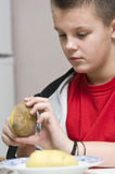 Boy helping mum in kitchen. A teenage boy helping his mother in the kitchen, peeling potatotes Royalty Free Stock Photo