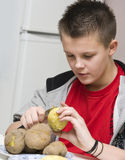Boy helping mum in kitchen. A teenage boy helping his mother in the kitchen, peeling potatotes Stock Image