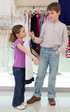 The boy helps girl to choose clothes in shop. Of childrens clothing Stock Images