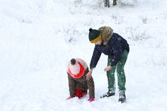 The boy helps the girl to climb out of the snow and move. On royalty free stock photography