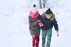 The boy helps the girl to climb out of the snow and move on. The boy helps the girl to climb out of the snow and move stock images