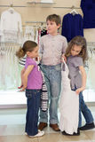 The boy helps girls to choose clothes in shop. Of childrens clothing, focus on boy royalty free stock photo