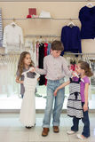 The boy helps girls to choose dress in shop. Of childrens clothing royalty free stock images