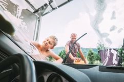 Boy helps his father with car washing stock photography