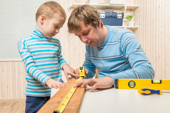 Boy helps his father in the work of carpenter Royalty Free Stock Images