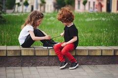 Boy helps little girl tie shoelaces. Cute boy helps little girl tie shoelaces royalty free stock images