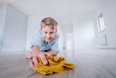 Boy helps make cleaning in new apartment after renovation Stock Image