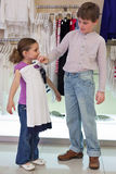 The boy helps sister to choose clothes in shop. Of childrens clothing royalty free stock photo