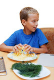 The boy helps to cook food. The boy helps to cook food at a table in kitchen Royalty Free Stock Photography