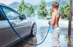 Boy helps to wash a car Stock Image