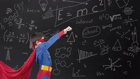 Boy in a hero costume on the school. Board stock image