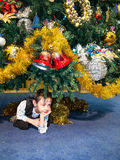 The boy hid under a tree. With bells Royalty Free Stock Photography