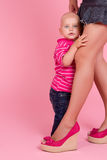 Boy hides behind mom feet. The boy hides behind mom feet, on a pink background Royalty Free Stock Image