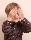 Boy Hiding. Small boy hiding his eyes and wearing a striped shirt Stock Images