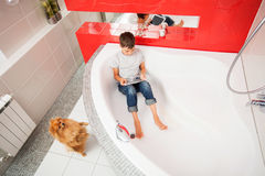 Boy hiding in the bathroom, playing in tablet Royalty Free Stock Images