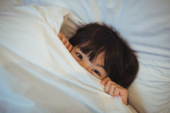 Boy hiding in bed under the blanket Stock Photos