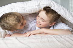 Boy hiding in bed under a white blanket or coverlet. Royalty Free Stock Image