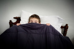 Boy hiding in bed. A young boy hiding  under the covers on his bed Stock Image