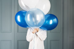boy hiding behind a bunch of balloons Stock Photography