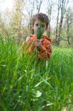 Boy hiding behind a fistful of grass. Child sitting in a grassy field hiding behind blades of grass Royalty Free Stock Photo