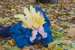 Boy hiding behind the leaf Autumn Royalty Free Stock Image